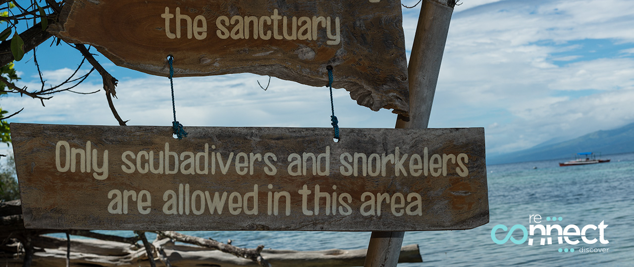 Wooden sign prohibiting passage to anyone but snorkelers and div
